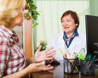 Зрелый доктор советуя с женским пациентом Стоковое фото RF