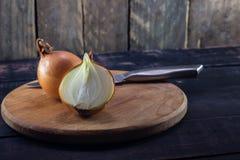 Зрелый отрезанный лук с ножом на деревенской деревянной предпосылке Стоковые Изображения RF