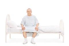 Зрелый пациент в мантии больницы сидя на кровати Стоковая Фотография RF