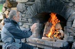 Зрелый подогрев человека с камином Стоковая Фотография
