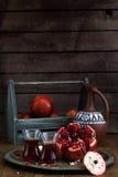 Зрелый плодоовощ гранатового дерева с соком гранатового дерева на медной плите и коробке и кувшине плодоовощ на деревянной винтаж Стоковые Изображения RF