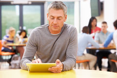 Зрелый студент изучая в классе с таблеткой цифров стоковые фото