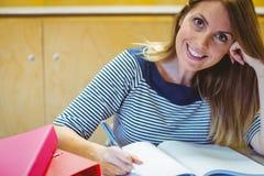 Зрелый студент принимая примечания в лекционном зале стоковое фото