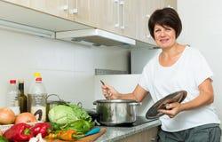 Зрелый суп женщины Стоковая Фотография