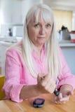 Зрелый уровень сахара в крови испытания женщины дома Стоковые Фото