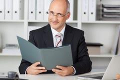 Зрелый файл удерживания бизнесмена на столе офиса Стоковые Изображения RF