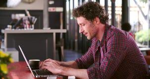 Зрелый человек в кафе работая на компьтер-книжке сток-видео