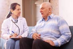 Зрелый человек жалуясь к доктору около чувствует Стоковая Фотография