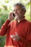 Зрелый человек используя мобильный телефон дома Стоковое Изображение