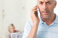 Зрелый человек используя мобильный телефон с газетой чтения женщины в предпосылке Стоковая Фотография