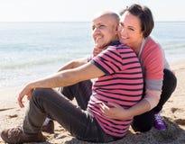 Зрелый человек и женщина сидя около моря на солнечном дне Стоковое фото RF
