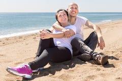 Зрелый человек и женщина сидя около моря Стоковые Изображения RF