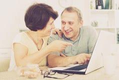 Зрелый человек и женщина смотря компьтер-книжку Стоковое Фото