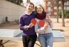 Зрелый человек и женщина с ракетками для настольного тенниса Стоковое фото RF