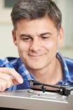 Зрелый человек кладя показатель винила на игрока стоковое фото