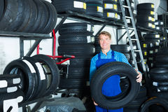 Зрелый человек механика стоя с новыми автошинами автомобиля Стоковое Фото