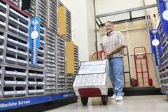 Зрелый человек нажимая handtruck в магазине оборудования Стоковая Фотография