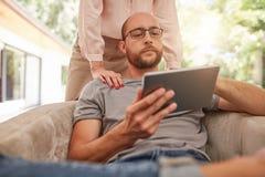 Зрелый человек дома используя цифровую таблетку Стоковое Фото