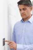 Зрелый человек поворачивая выключатель дома Стоковая Фотография