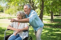 Зрелый человек при женщина сидя в кресло-каталке на парке Стоковое Изображение RF