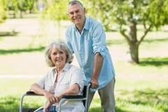 Зрелый человек при женщина сидя в кресло-каталке на парке Стоковые Фото