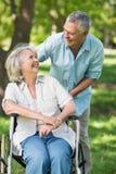Зрелый человек при женщина сидя в кресло-каталке на парке Стоковая Фотография