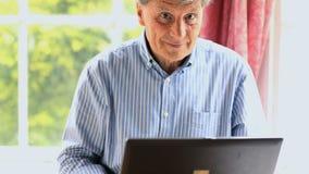 Зрелый человек сидя окном используя его компьютер сток-видео