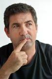 Зрелый человек думая с одним пальцем на его губах Стоковые Фото