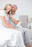 Зрелый человек целуя щеку женщины в кровати Стоковые Изображения RF