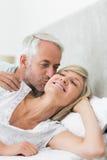 Зрелый человек целуя щеку женщины в кровати Стоковые Фотографии RF