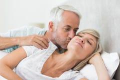 Зрелый человек целуя щеку женщины в кровати Стоковая Фотография