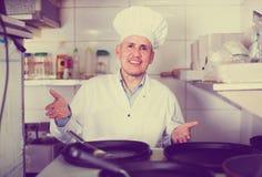 Зрелый шеф-повар с сковородами в кухне Стоковые Изображения