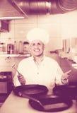 Зрелый шеф-повар с сковородами в кухне Стоковое Фото
