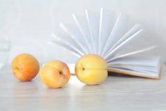 3 зрелых абрикоса на предпосылке открытых страниц книги Стоковые Фото