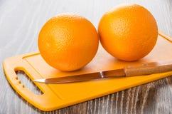 2 зрелых апельсины и кухонного ножа на пластичной разделочной доске Стоковое Изображение RF