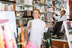 2 зрелых аптекаря стоя рядом с полками Стоковое Изображение