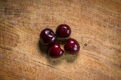 4 зрелых вишни на деревянной планке Стоковые Изображения