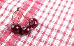 3 зрелых вишни на салфетке шотландки Стоковые Фото