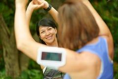 2 зрелых женщины держа пригонку и streching перед jogging Стоковые Фото