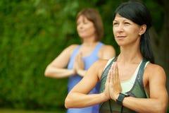 2 зрелых женщины держа пригонку путем делать йогу в лете Стоковые Фотографии RF
