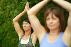 2 зрелых женщины держа пригонку путем делать йогу в лете Стоковые Фото