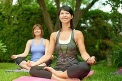 2 зрелых женщины держа пригонку путем делать йогу в лете Стоковые Изображения