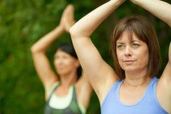 2 зрелых женщины держа пригонку путем делать йогу в лете Стоковая Фотография