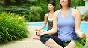 2 зрелых женщины держа пригонку путем делать йогу в лете Стоковое Фото
