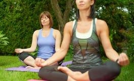 2 зрелых женщины держа пригонку путем делать йогу в лете Стоковое фото RF
