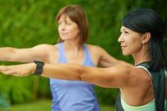 2 зрелых женщины держа пригонку путем делать йогу в лете Стоковые Изображения RF