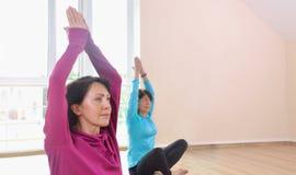 2 зрелых женщины делая йогу работают в студии фитнеса Стоковое Изображение RF
