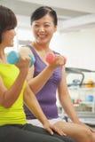 2 зрелых женщины поднимая весы в спортзале Стоковое Изображение