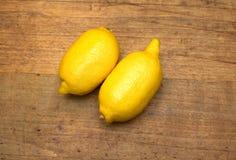 2 зрелых желтых лимона лежат на деревянной поверхности Стоковые Фотографии RF
