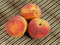 3 зрелых красно-желтых персика на плетеной циновке соломы Стоковая Фотография